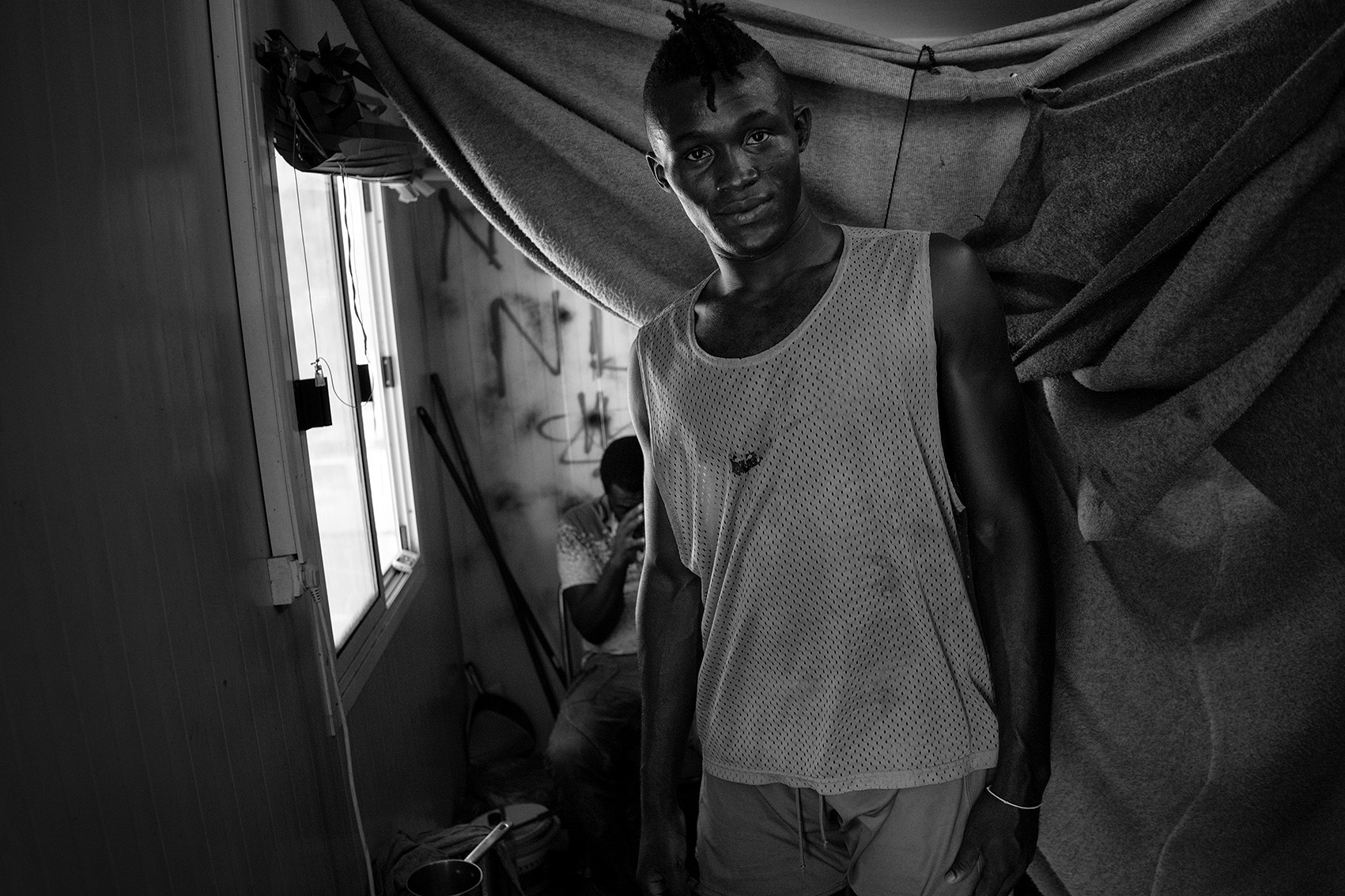 Ali, a professional football player from Guinee, inside his container at the refugee camp Moria, Lesbos, Greece