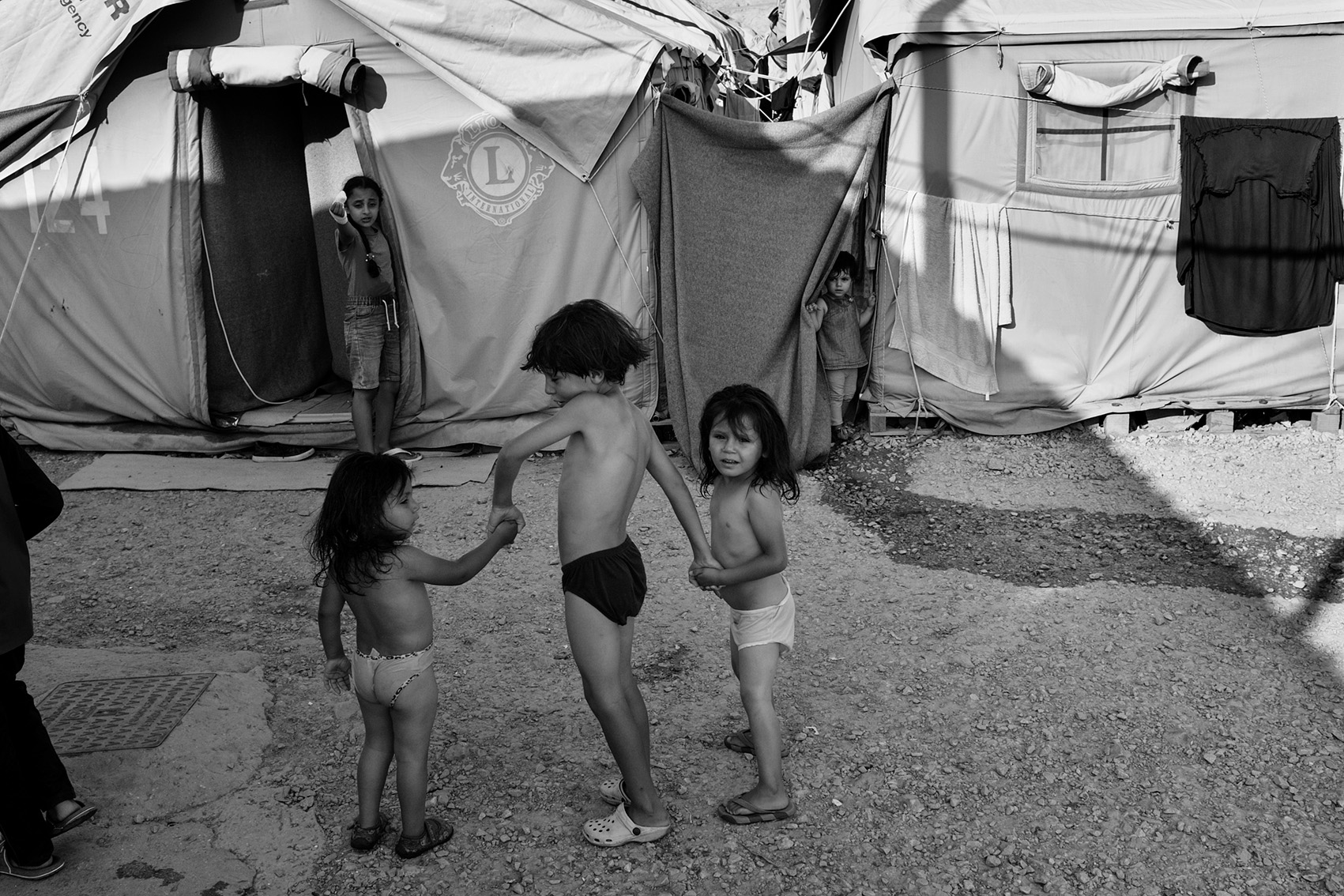 Children walking hand-in-hand inside refugee camp Moria, lesbos, Greece