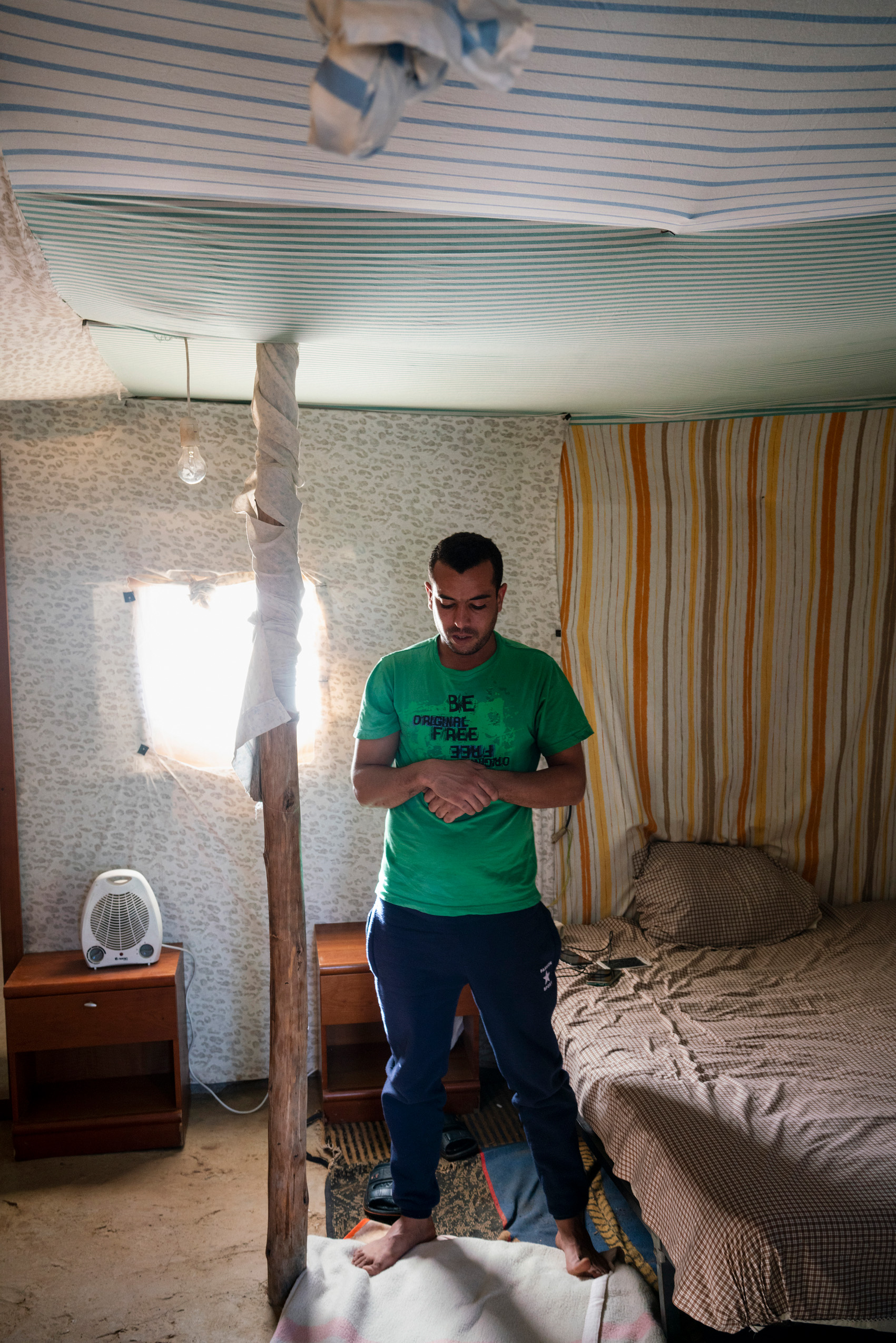 Ahmedi is a 32-year old Moroccan electrician who lived in Italy for 10 years before coming to Spain 3 years ago. He is praying in his self-constructed house made of plastic sheets, Spain.