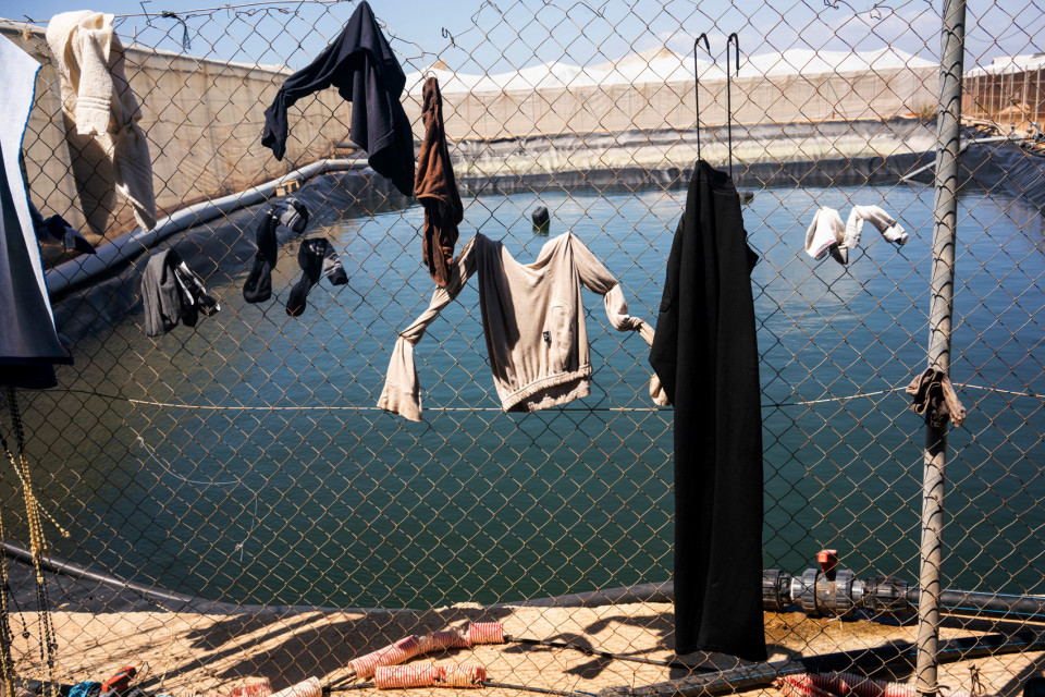 Workers hang their washing to dry on a fence at the nearby barn, Spain.
