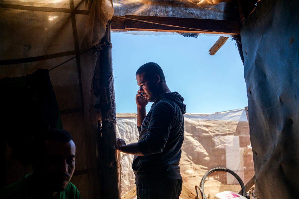 A Moroccan migrant worker living in a ghetto of self-constructed houses made of plastic sheeting, Spain.