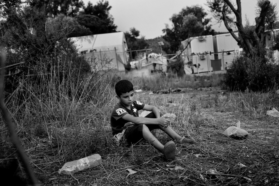 A Syrian young boy who came with his parents and 2 sisters just outside the back of the refugee camp Moria where they prepare their dinner on a wood fire. Lesbos, Greece