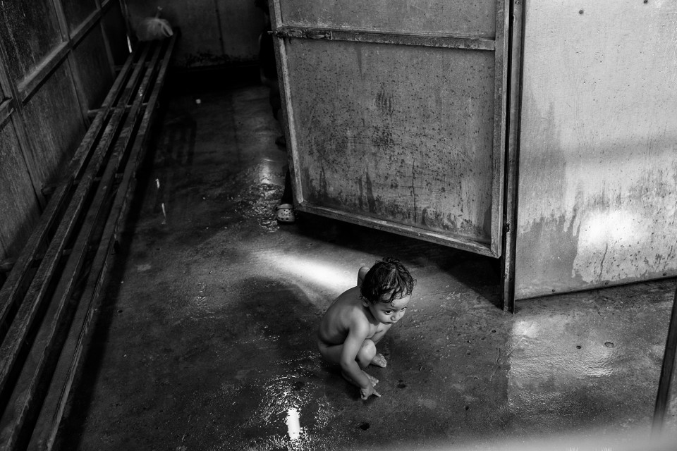 A Syrian boy at a shower inside the refugee camp Moria, Lesbos, Greece.