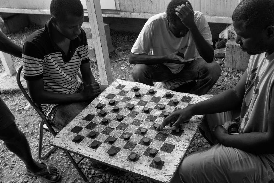 Africans are playing checkers inside the refugee camp Moria, Lesbos, Greece
